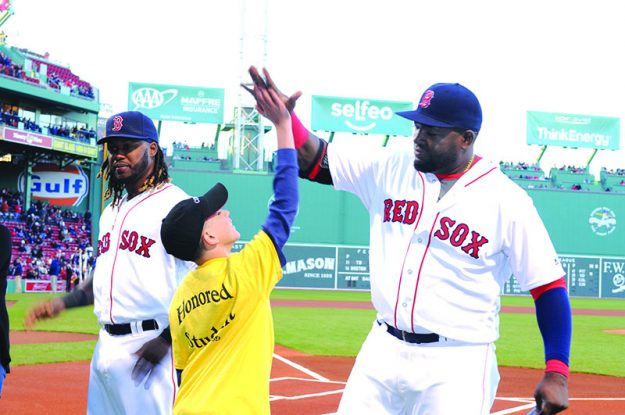 """➥➥ Yhan Cruz Maldonado student of the Browne School in Chelsea high fives David """"Big Papi"""" Ortiz during the first Latino Youth Recognition Day at Fenway Park."""