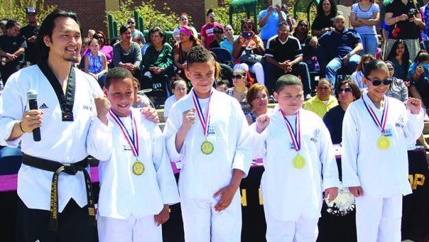 ➥➥ Master Hans Kim posa con estudiantes que ganaron medallas por mejorar académicamente desde que empezaron a participar en el programa de Taekwondo en la Escuela South Lawrence East School. Ellos son Luis Martínez, Daniel Torres, Anven Francisco y Jhonsy Perdomo.