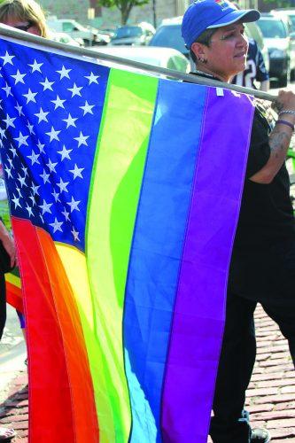 ➥➥ Neida Pérez sostiene la bandera multicolor durante la vigilia en el parque Campagnone de Lawrence en memoria de las victimas de Pulse Nightclub en Orlando, Florida.