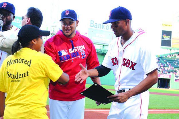 ➥➥ Eduardo Rodríguez y Xander Bogaerts felicitan a la estudiante Gabriella Acosta de la Parthum Middle minutos antes del juego entre los Red Sox y los White Sox.