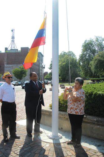 ➥➥ El Alcalde de Lawrence iza la bandera colombiana con la ayuda de Luz Echeverry en el Parque Campagnone el pasado 20 de julio.