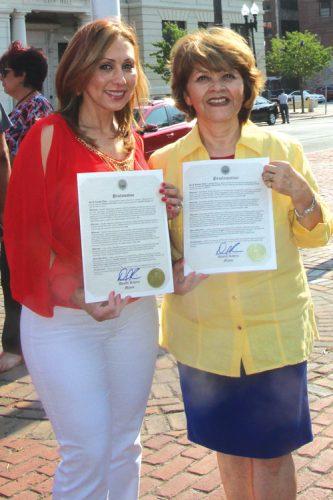 ➥➥ Claudia Hoyos (a la izquierda) y Carmenza Bruff muestran la proclama que les entregó el Alcalde de Lawrence Daniel Rivera por su trabajo en el ámbito cultural y de servicios humanos.
