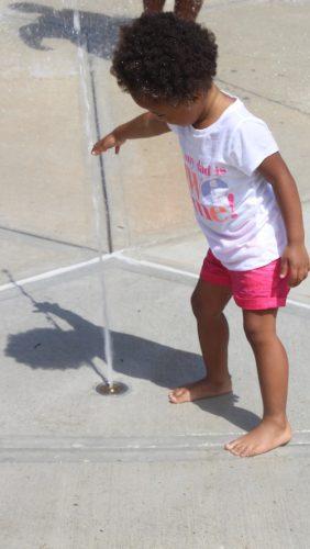 : Mia Andrea Mercedes Cruz toca uno de los chorros en el parque de agua en Lawrence. Foto por Yadira Betances.