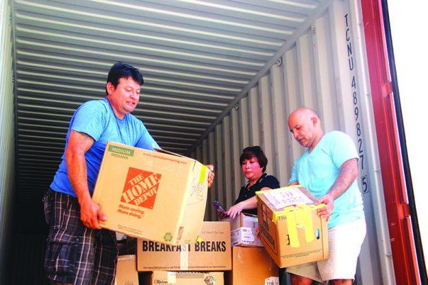 ➥➥ Angel Fernández a la izquierda y Luis Yépez acomodan las cajas en el contenedor con la ayuda de Alexandra Serrano. Foto por Yadira Betances.