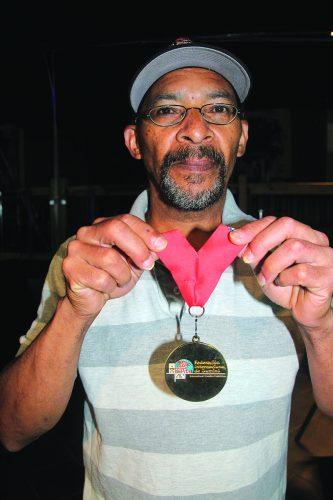 ➥➥ Franklyn Almonte muestra la medalla que ganó durante la competencia Mundial de Dominó en la Florida.