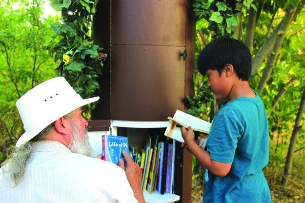 ➥➥ Wayne Hayes le enseña uno de los libros a Tristan Namen de la Biblioteca Libre, localizada en Jacques Pond en la calle Genesee al sur de Lawrence.