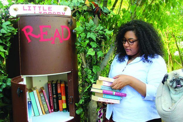 ➥➥ Verónica Piña coloca libros que donó a la biblioteca libre localizada en Jacques Pond en la calle Genesee al sur de Lawrence.