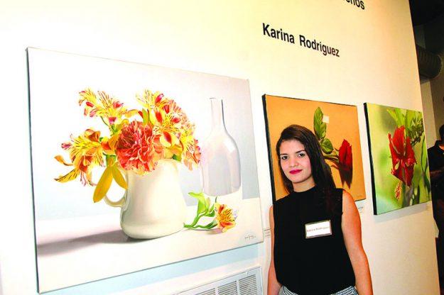 """➥➥ Karina Rodríguez posa delante de dos de sus obras en la exposición """"Tonos Caribeños""""."""