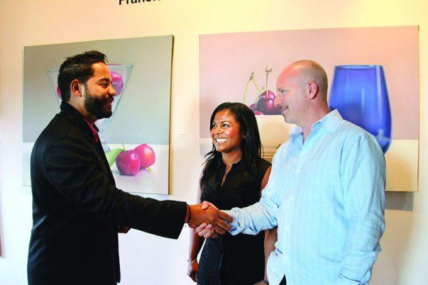 ➥➥ El pintor Francisco Collado saluda a Gary Sidell, propietario de Bell Tower Management y a Janin Durán directora del programa hispano de EforAll.