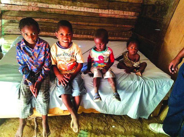 ➥➥ Niños que antes dormían en el suelo, están contentos porque recibieron como regalo la cama sobre la que están sentados.