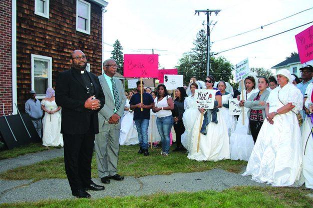 ➥➥ Los ministros Joel Almonó y Victor Jarvis hacen una oración en frente de la casa de la difunta Wanda Rosa en Methuen como parte de la Marcha de las Novias.