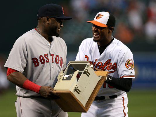 Adam Jones (derecha) de los Orioles de Baltimore entrega a David Ortiz de los Medias Rojas de Boston con un teléfono que destruyó en la temporada de 2013, el jueves 22 de septiembre de 2016. Foto: AP