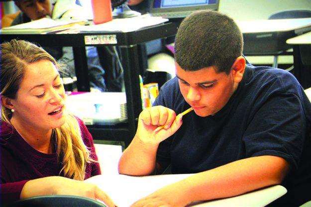 ➥➥ La maestra de séptimo grado Blake Orban ayuda a Rudy Guzmán durante una clase de matemáticas en la Spark Academy, parte de la escuela South Lawrence East School.