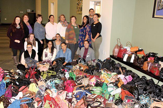 Empleados de Elder Services of Merrimack Valley posan junto con las 355 bolsos y mochilas que colectaron.