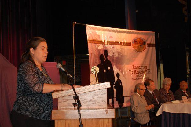 La Directora de Educación de las Naciones Unidas en Boston, Caitlin Moore, le habla a los estudiantes. En el panel estaban la Superintendente de las Escuelas Públicas, Catherinna Latham, los dos sobrevivientes del holocausto,  el director del Comité Judío Americano, Robert Leikind y el Jefe de la Sección en Derechos Civiles de la Oficina de la Fiscal General, Jonathan Miller.